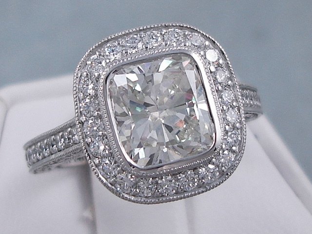Engagement ring featuring a cushion cut diamond and multiple smaller diamonds