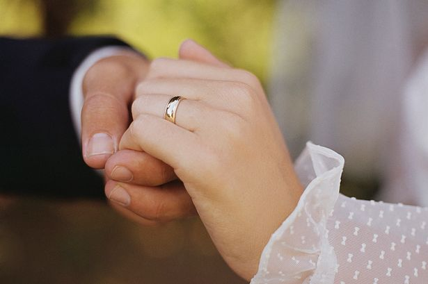 Wedding ring on couples hand