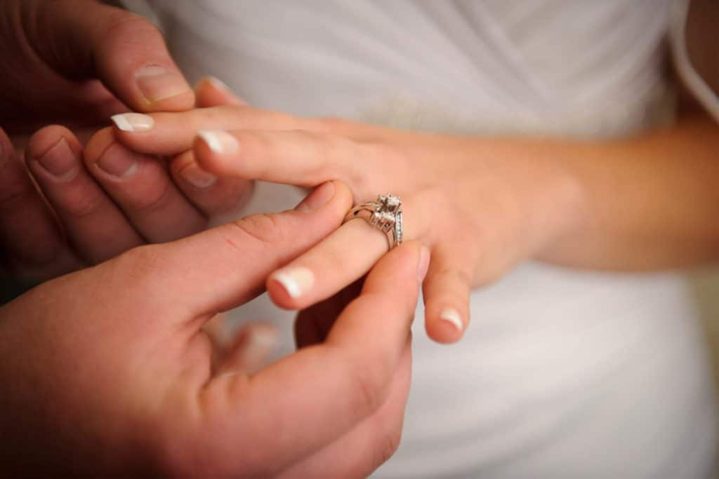 man putting a ring on a woman's finger